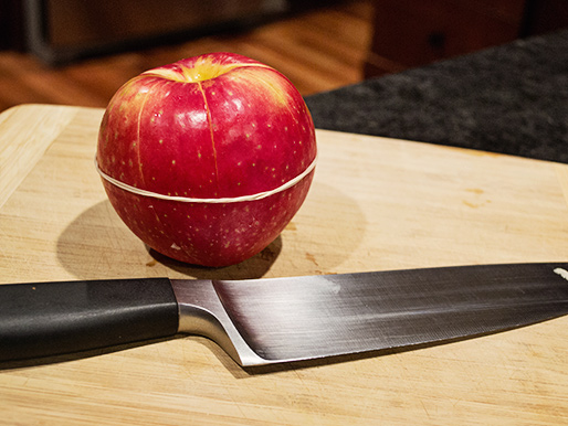 An apple cut into slices bound with a rubber band for easy storage, carrying and freshness.