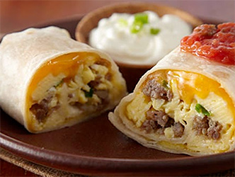 egg and sausage breakfast burritos on plate with sour cream and salsa