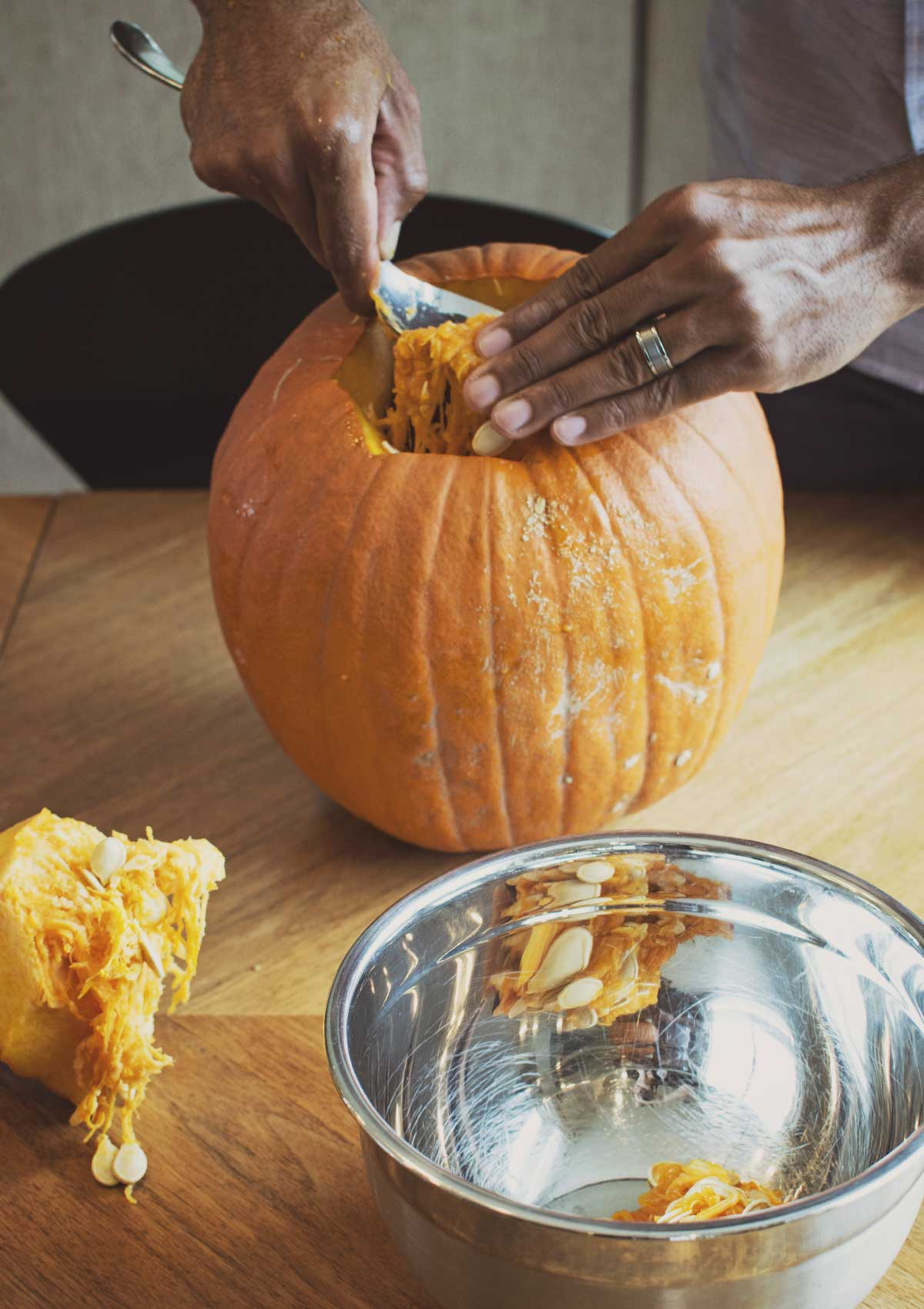 Scooping out a large Halloween pumpkin with a large spoon.
