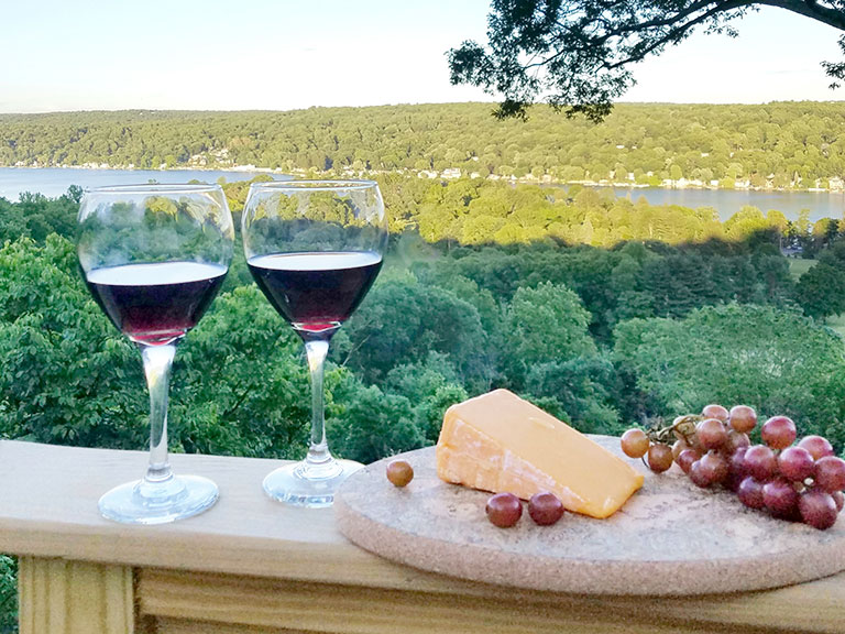 wine cheese and grapes on wooden deck with trees and lake in background